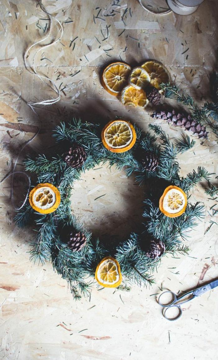 ideas de manualidades con piñas decoradas, guirnalda de navidad con frutas secas y piñas