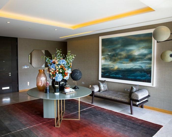 ideas de decoracion recibidores modernos, alfombra en rojo y gris, paredes con pintura grande, detalles decorativos y flores