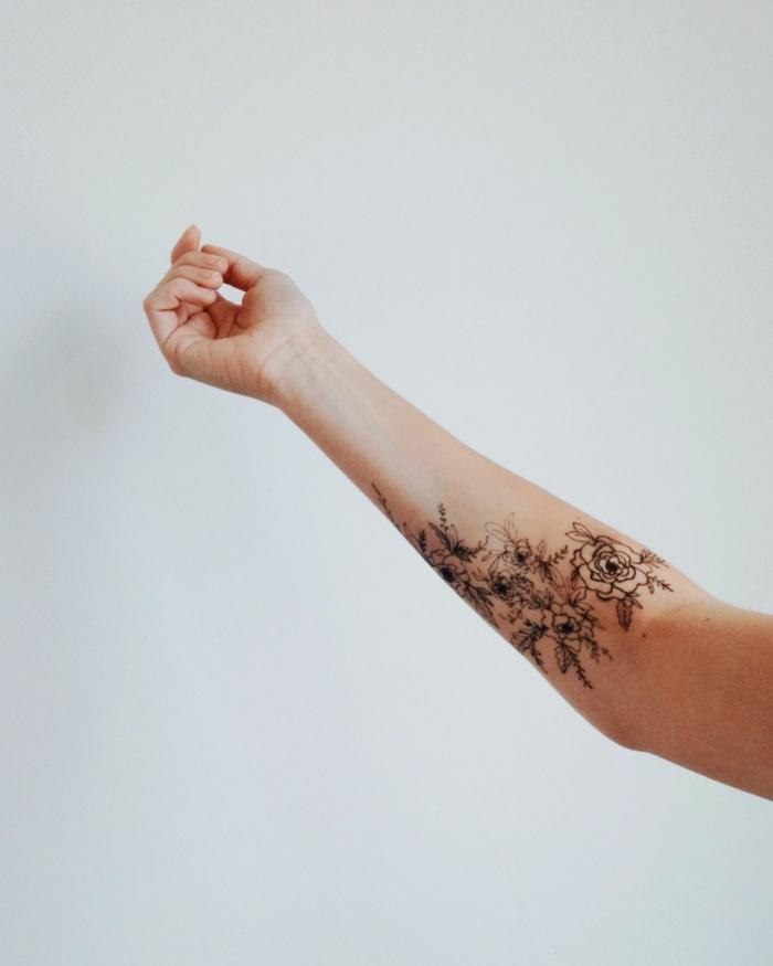 ejemplos de tatuajes en el antebrazo para las mujeres, flores tatuadas con tinte negro, tattoos con significado