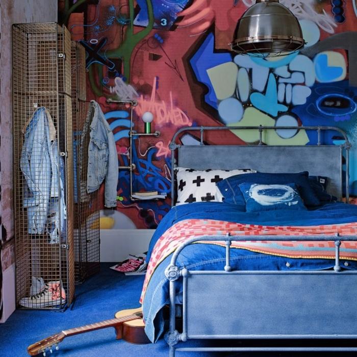 decoracion apartamentos pequeños, cama azul de metal con pared de graffitis y guitarra en el suelo