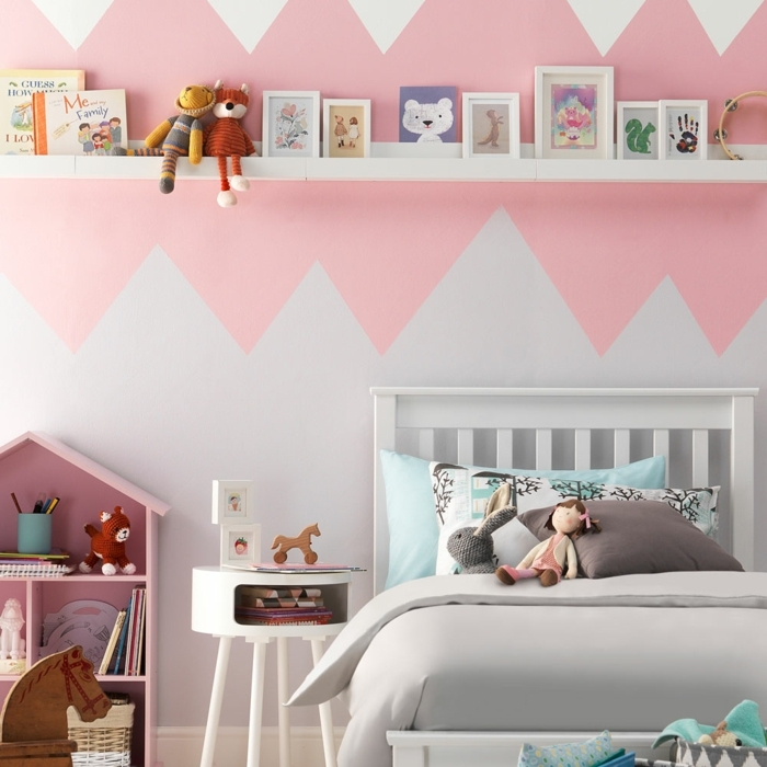 literas juveniles, pared en blanco y rosa con figuras de colores, estantería blanca con marcos para fotos