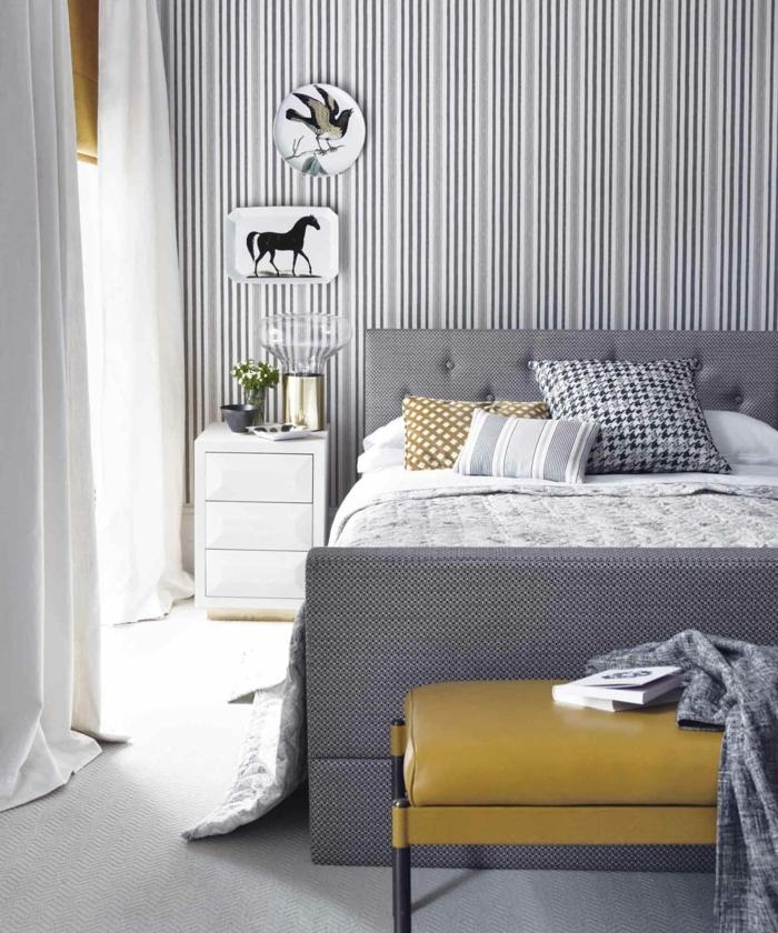 decoracion apartamentos pequeños, cama gris con cabecera alta con vinilo de rayas verticales