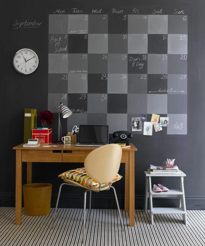 dormitorios infantiles, pared con colendario de pizarra en gris y negro, escritorio de madera con silla en beige