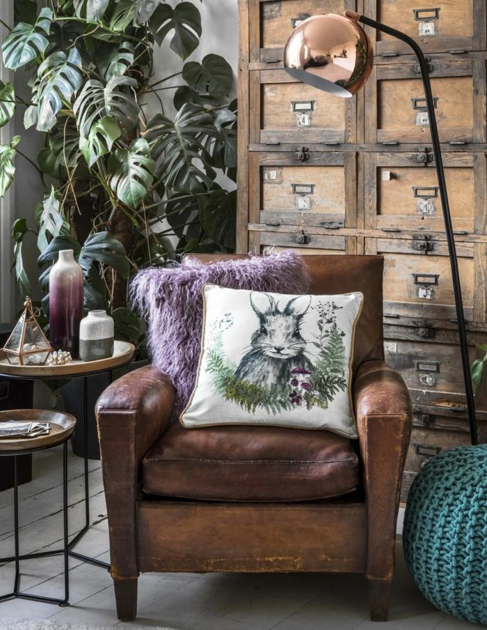 decoracion apartamentos pequeños, sillón de cuero marrón con cojines en blanco y azul con conejos