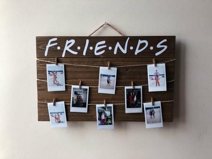 que le puedo regalar a mi mejor amiga, cartel de madera con cuerdas y fotos colgadas en el con pinzas de madera