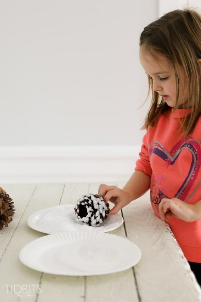 manualidades con piñas para pequeños y adultos, piñas con decoración efecto nieve paso a paso
