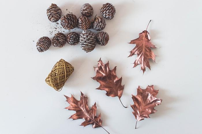 materiales necesarios para hacer una guirnalda para decorar la casa en otoño, piñas, hilo dorado, hojas secas pitnadas