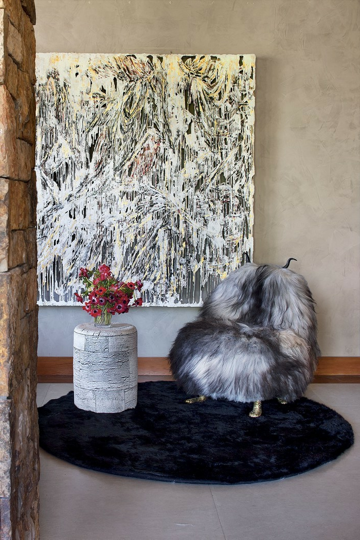 pequeño recibidor decorado con encanto, alfombra en negro de forma oval, grande pintura en la pared, recibidores pequeños