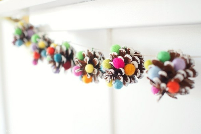 guirnalda de piñas pintadas en blanco edecto ombre con pompones coloridos pequeños, como hacer manualdiades paso a paso