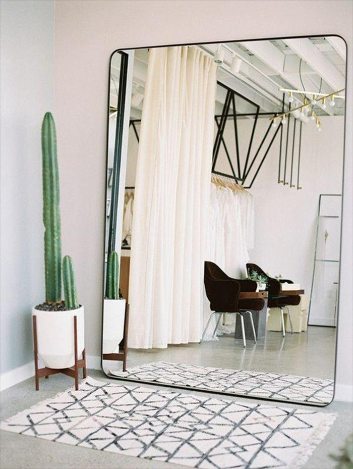 mueble recibidor modernos, grande espejo apoyado en la pared, alfombra pequeña ornamentada