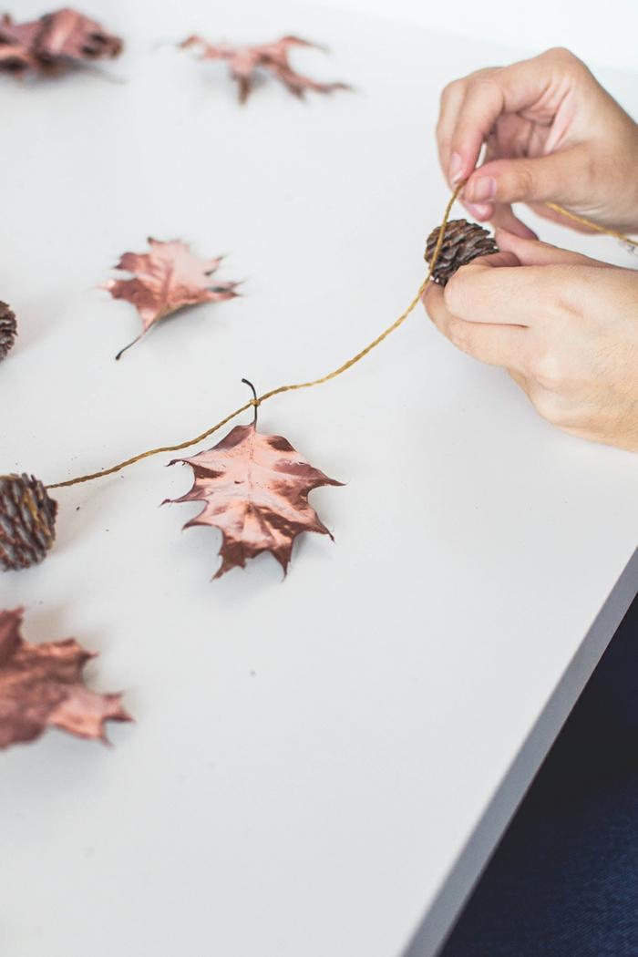 como hacer una guirnalda de hojas secas pintadas en tono metálico, piñas e hilo dorado, manualidades faciles de hacer