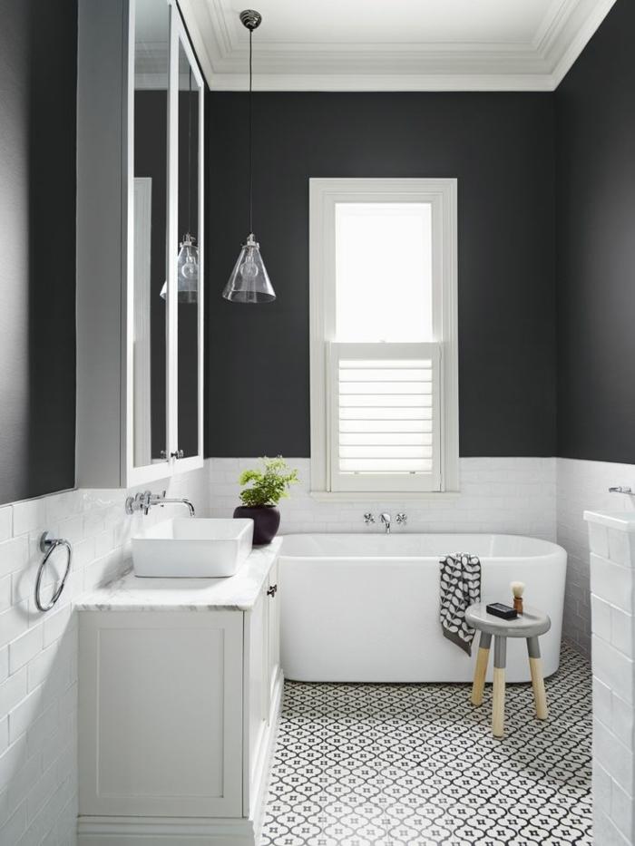alicatar baños, bañera de color blanco con toalla sobre ella, silla de madera pintada de gris, pared negra