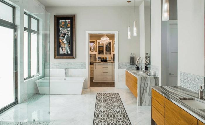 grande baño con bañera moderna en blanco, alfombra ornamentada blanco y gris, cabina de cucha con vitrina de vidrio