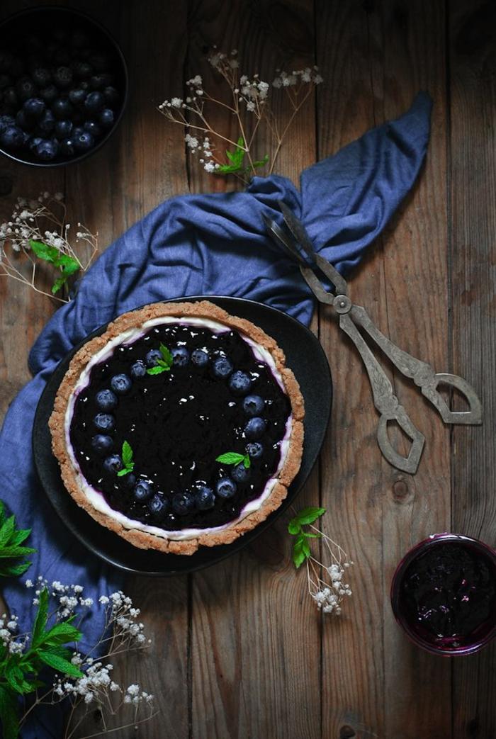 preciosa tarta de queso philadelphia sin horno con mermelada de frutas adornada con arándanos y hojas de menta