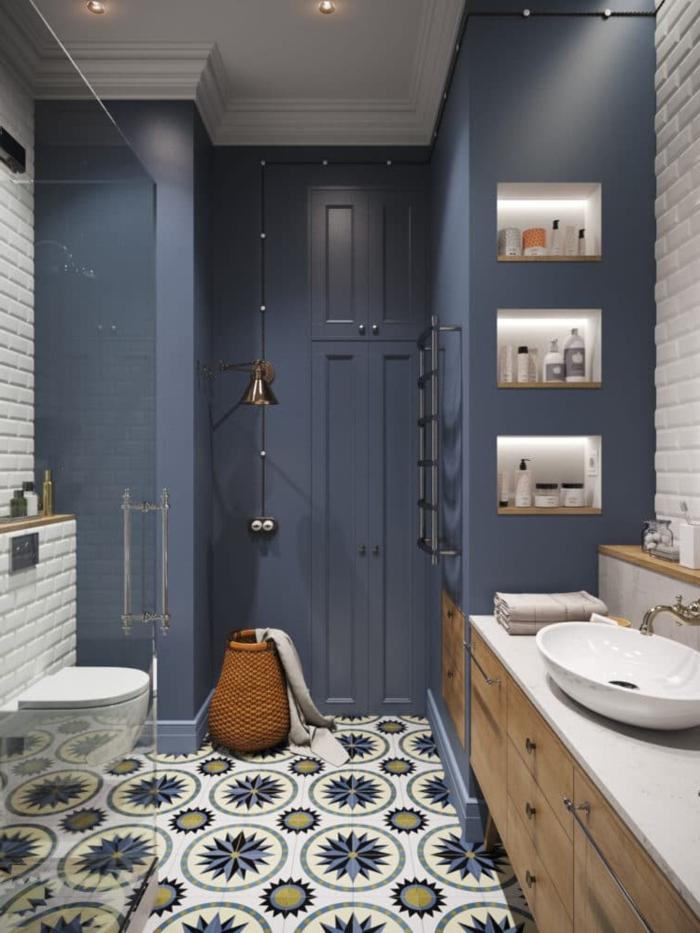 azuejos de baño suelo con baldosas con figuras geométricas, paredes en azul pastel, lavabo blanco