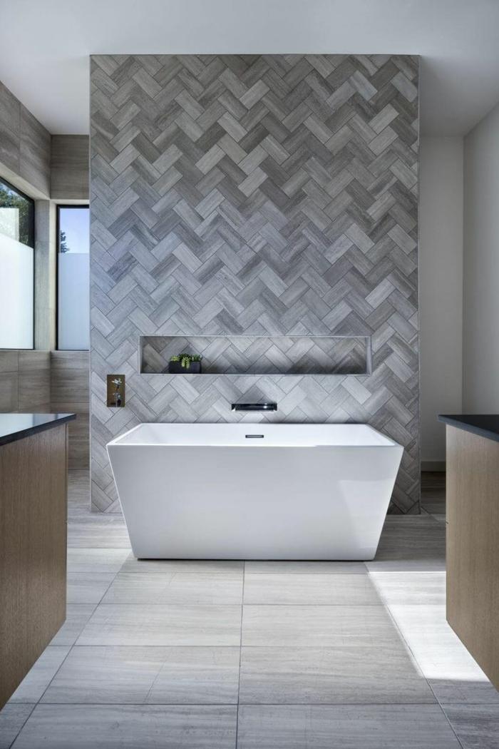 azulejos de baño, una pared con baldosas en diferentes tonalidades del gris, bañera blanca, suelo gris