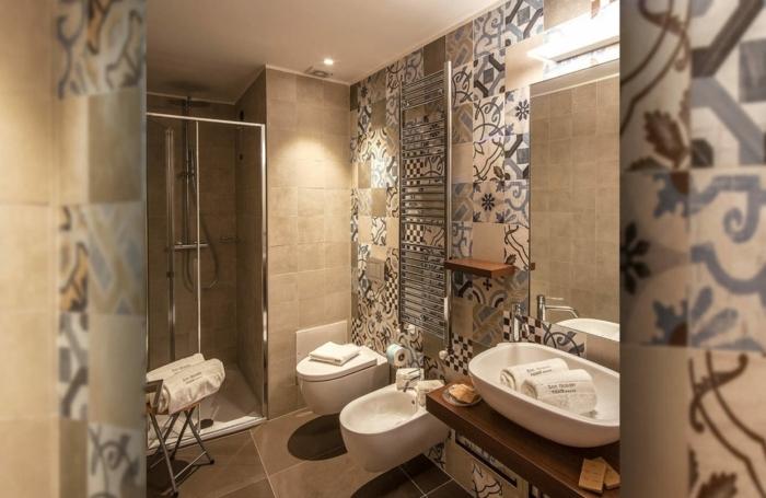 azulejos de baño, baldosas de motivos etnicos de colores en beige y azul, espejo, bidé y mampara de cristal
