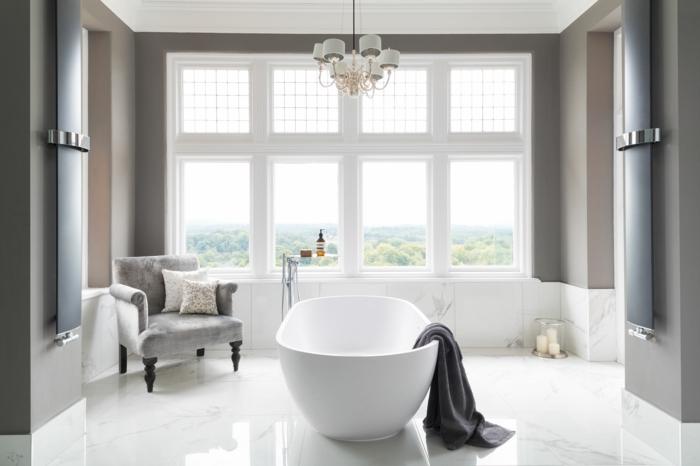 azulejos imitacion madera, bañera blanca con toalla gris colgando en ella, ventana grande en toda la pared