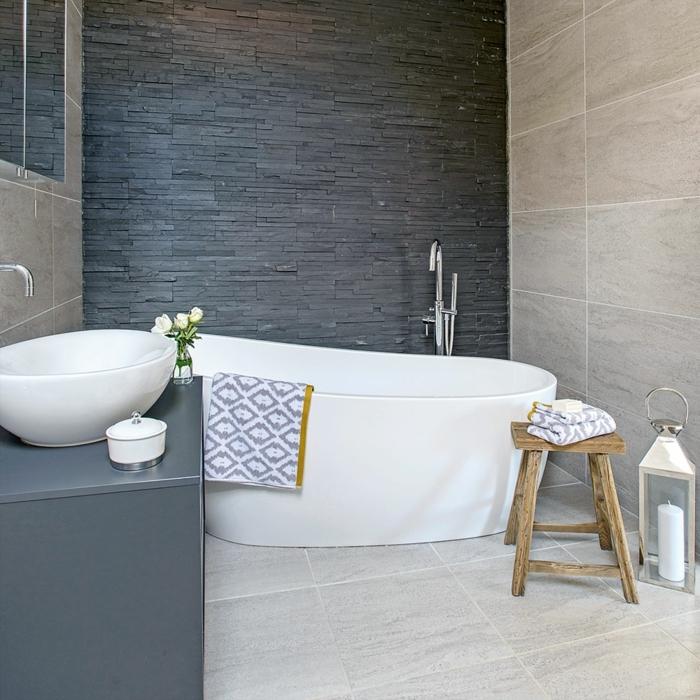 azulejos imitacion madera , bañera blanca con toalla de figuras grises en ella, silla de madera, paredes en gris y beige