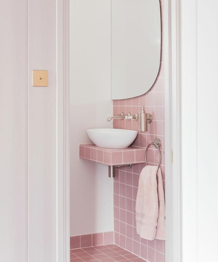 azulejos para baños de color rosa, con toalla rosa, espejo y lavabo pequeño de color blanco