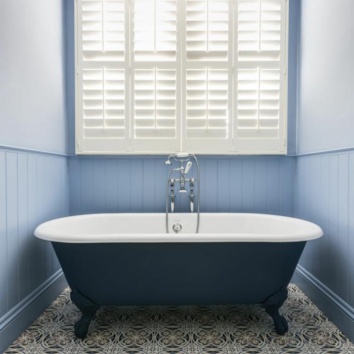 azulejos para baños, bañera de color negro, con suelo de baldosas de motivos étnicos, ventana grande