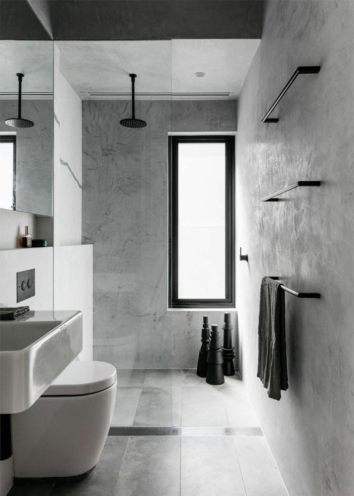 baldosas baño de color gris y negro con ventana larga de color negro, toalla negra, espejo y lavabo blanco