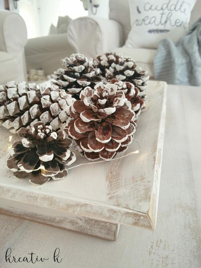 ideas de decoracion navideña manualidades, piñas pintadas en blanco con luces, centro de mesa DIY