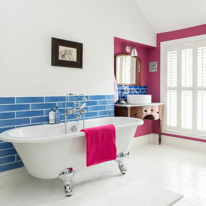 ceramicas para baños, bañera de color blanco con toalla rosa fucsia en ella, baldosas azules como ladrillos