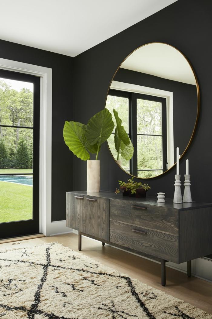 entraditas modernas decoradas con encanto, grande espejo oval en dorado, alfombra en beige, pared pintada en negro