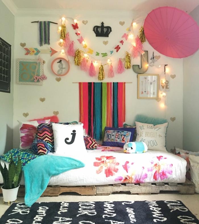 como decorar una habitacion pequeña, alfombra negra con inscripciones blancas, cama de palets