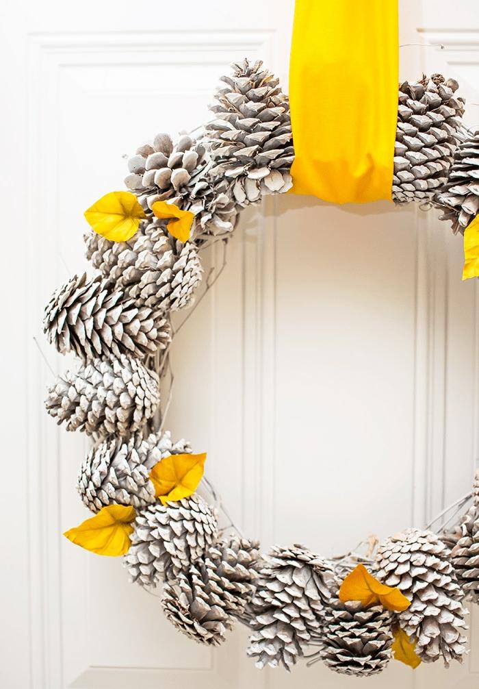 preciosa decoracion navideña manualidades, guirnalda nevideña DIY de piñas para colgar en la puerta