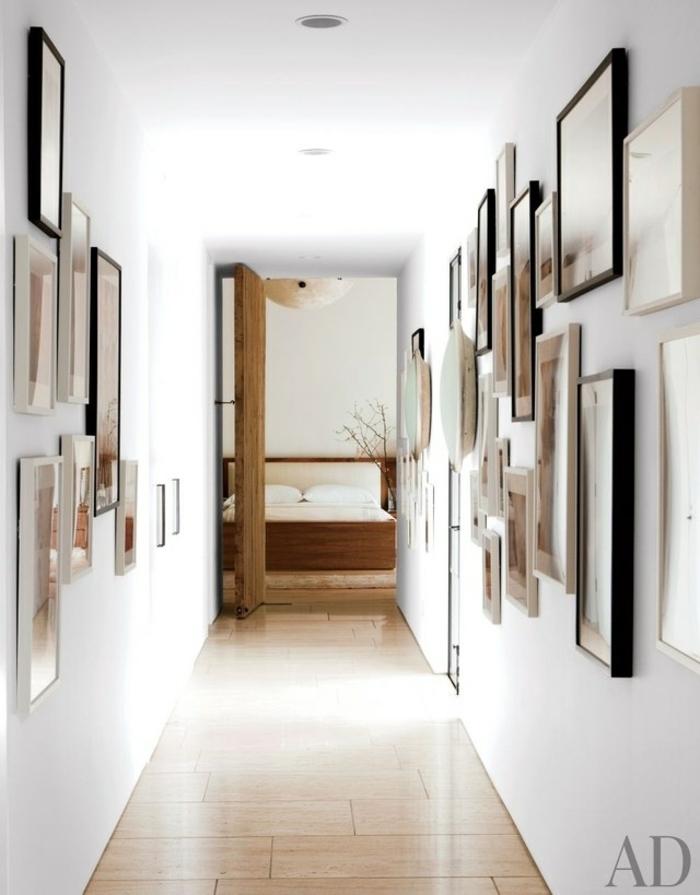 corredor estrecho y moderno con paredes cubiertas de cuadros decorativos, muebles recibidor estrecho