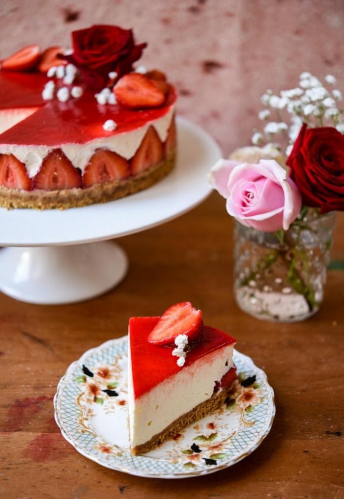 postres ricos decorados con encanto, tarta de queso con fresas y glaseado rojo, decoración con flores