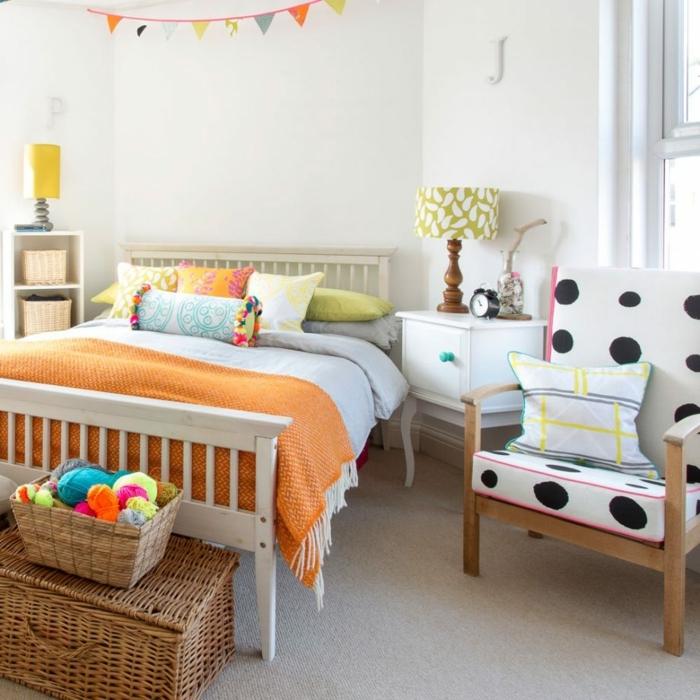 decoracion pisos pequeños, sillón blanco con tela de lunares negros, cojín en el sillón, cama blanca de madera