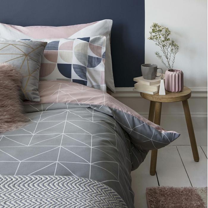 decoracion pisos pequeños, cama con sábanas en gris y rosa con figuras geométricas, mesa de madera