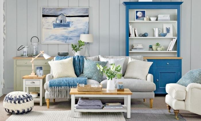 decoracion pisos pequeños, sofa en gris claro con cojines en blanco, azul y amarillo, otomana en el suelo