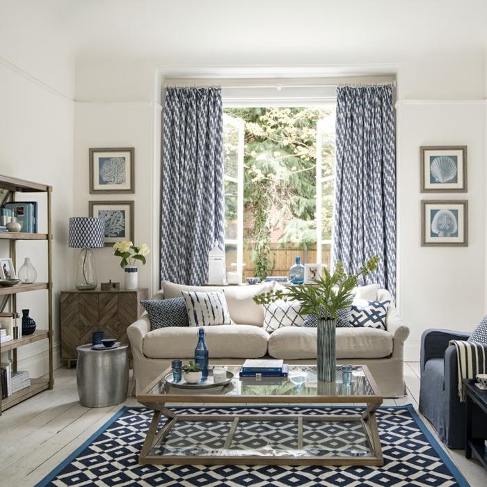 decoracionsalon pequeño, sof´en color crema con cojines de colores, cortinas en azul y blanco de tela
