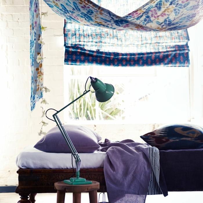 decoracionsalon pequeño, cama con sábanas en lila, lámpara en verde, ventana grande