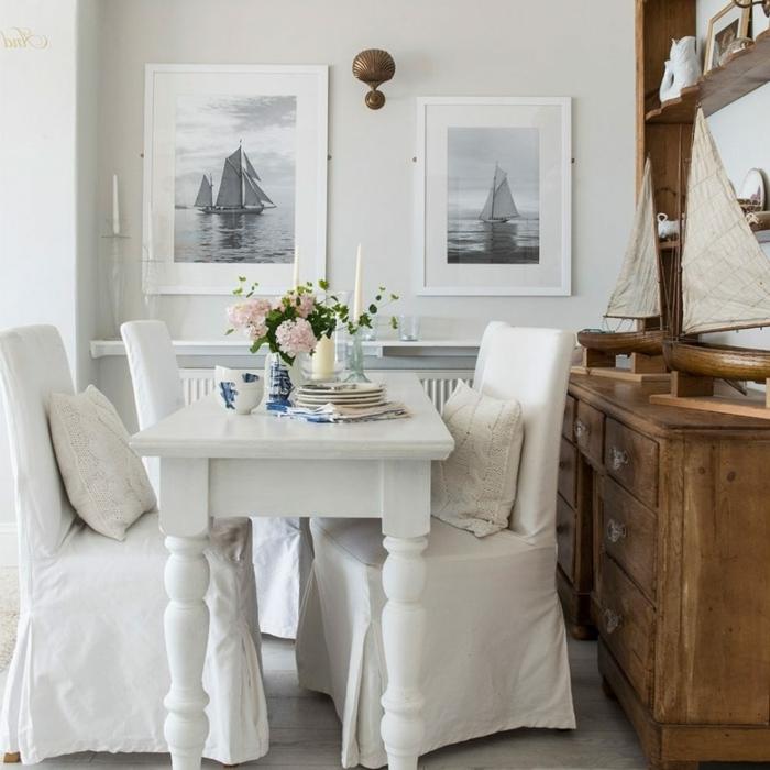 decoracion salon pequeño, mesa de comer blanca con sillas de tela blanca y cuadros de barcos