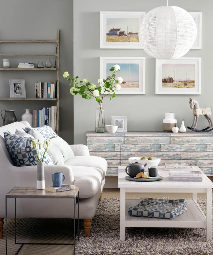 decorar salon pequeño, cuadros en la pared con marcos blancos, lámpara esférica y mesa blanca