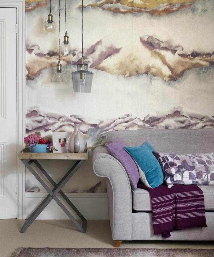 decorar salon pequeño, sofá en gris claro con almohadas de colores y manta en el, lámparas colgantes