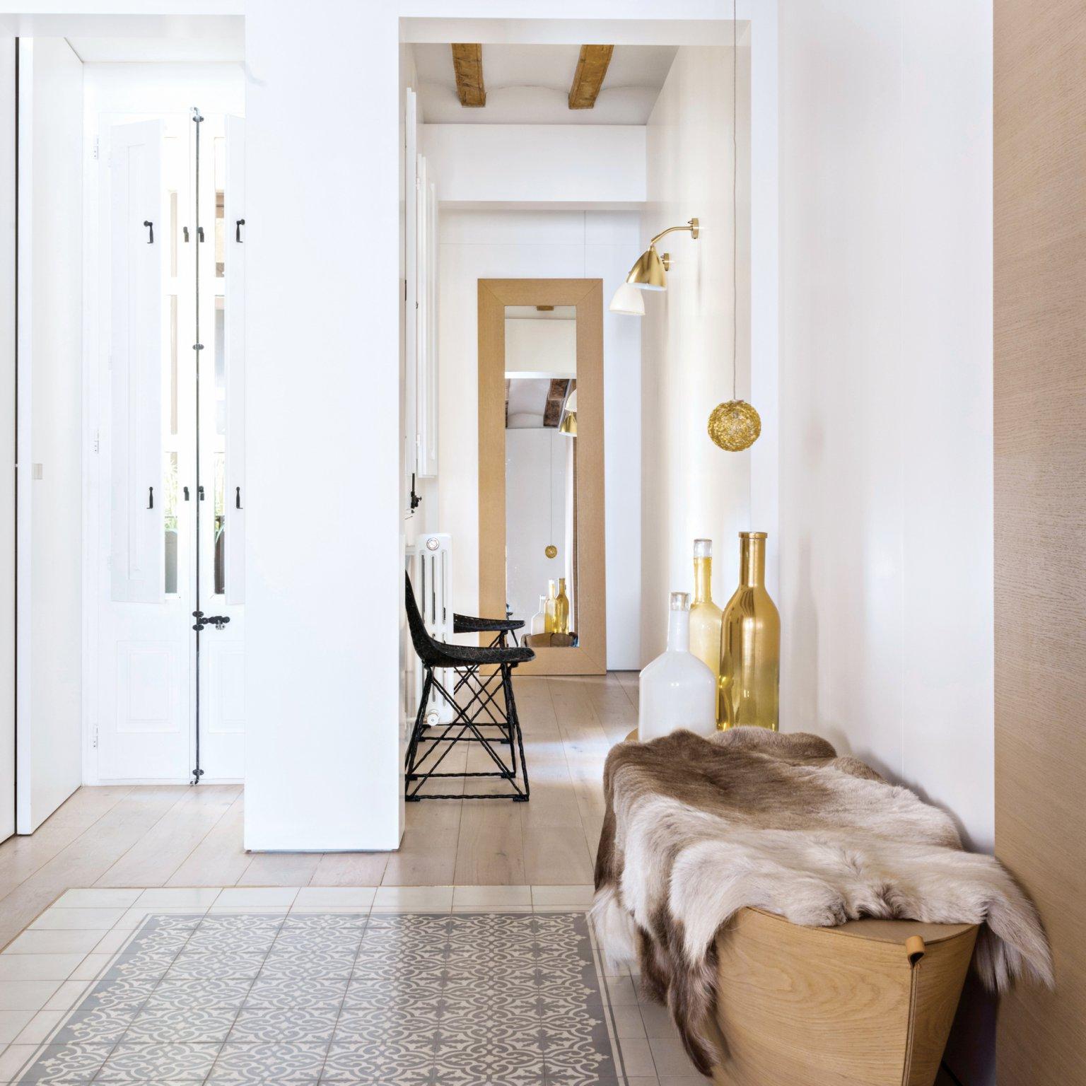 precioso recibidor decorado en tonos claros, banco de madera, paredes en blanco y detalles en dorado