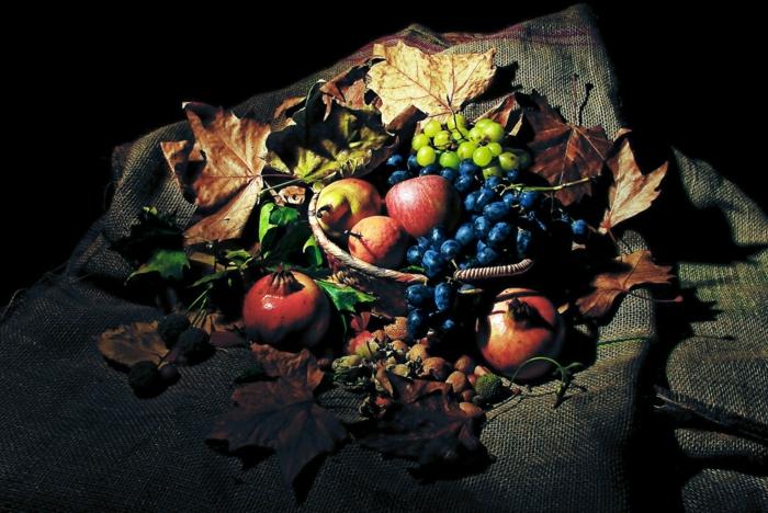 fotos de otoño gratis, en un mantel frutas y hojas de otoño, manzanas, uvas en azul y verde y pomegranate