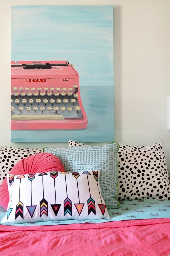 habitaciones juveniles , cuadro con máquina de escribir rosa en el fondo azul claro, cojines de colores