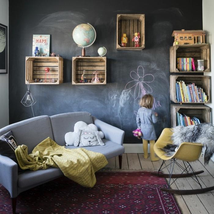 habitaciones juveniles modernas, niña pintando en la pizarra establecida en roda la pared, cajas en ella, niña