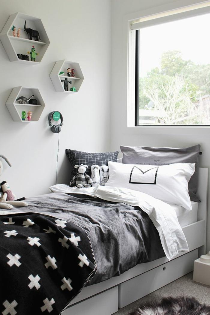 habitaciones juveniles niña, cama con sábanas en negro, blanco y gris con estanterías en la pared