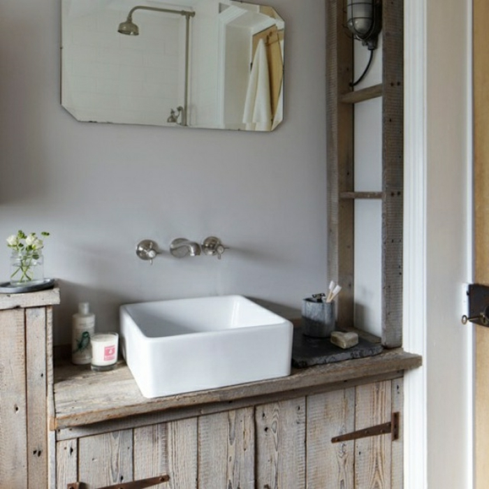 pequeño baño decorado en estilo rústico, armario de madera y espejo vintage, paredes en gris claro