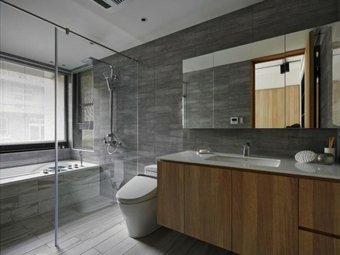 decoración de encanto baño grande, suelo de parquet, armario grande de madera y paredes con azulejos en gris