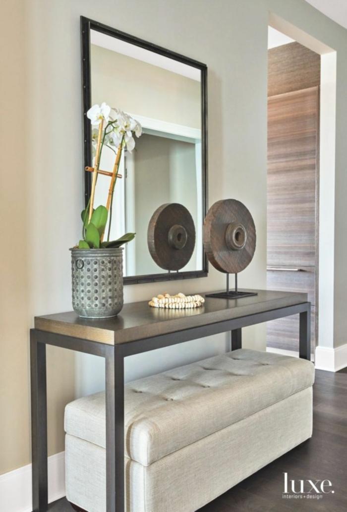 entraditas pequeñas decoradas de mucho estilo, banco en capitoné, mesa alta de madera y espejo colgado en la pared