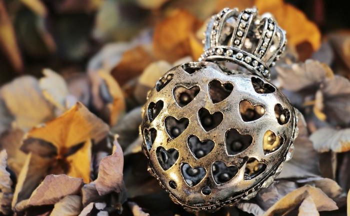 imagenes de otoño, corazon de metal con corona tirada en el suelo entre las hojas arrugadas